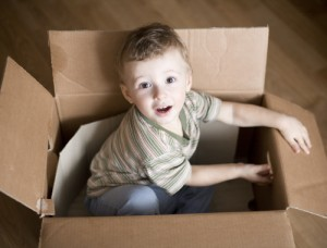Small boy playing in a cardboard box
