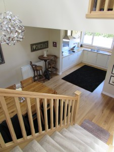 Wooden stairway to open plan dining area and kitchen